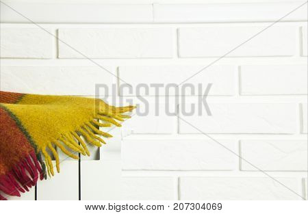 background - a brick wall with a white battery on which there is a multicolored plaid plaid. Copyspace