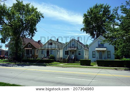 JOLIET, ILLINOIS / UNITED STATES - JULY 25, 2017: A row of small Cape Cod style houses, built very close together, on Broadway Street, in one of Joliet's less affluent neighborhoods.