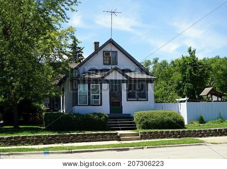 JOLIET, ILLINOIS / UNITED STATES - JULY 25, 2017: A small Cape Cod style home, with a tall television antenna, on Broadway Street, in one of Joliet's less affluent neighborhoods.