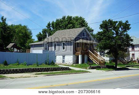 JOLIET, ILLINOIS / UNITED STATES - JULY 25, 2017: A small Cape Cod style home, with a high front porch, on Broadway Street, in one of Joliet's less affluent neighborhoods.