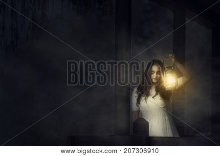 Spooky image of a scary woman with dark eyes and appearance of a witch in a white dress holding a lit lantern in a dark night atmosphere.