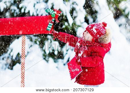Child With Letter To Santa At Christmas Mail Box In Snow