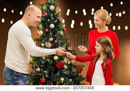family, holidays and people concept - happy mother, father and daughter decorating christmas tree over lights background