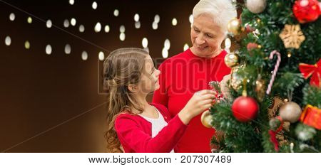 holidays, family and people concept - happy grandmother and granddaughter decorating christmas tree over lights background
