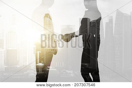 business, partnership and cooperation concept - businessman and businesswoman silhouettes shaking hands over city background