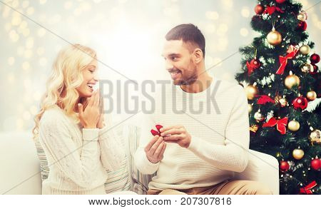 love, couple, proposal and people concept - happy man giving engagement ring in little red box to woman over christmas tree and lights background