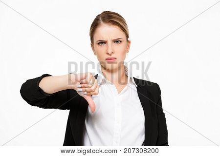 Displeased serious blonde business woman showing thumb down and looking at the camera over white background