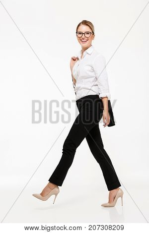 Full length side view image of smiling blonde business woman in eyeglasses walking in studio and looking at the camera over white background