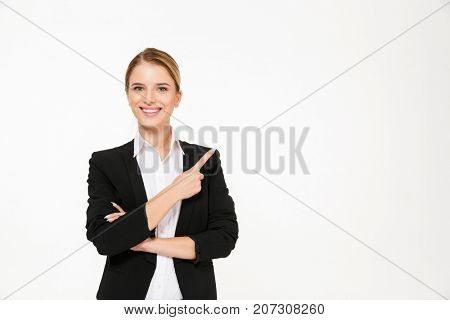 Smiling blonde business woman pointing away and looking at the camera over white background