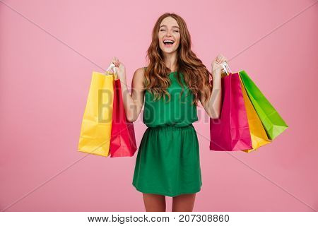 Portrait of a smiling satisfied woman in dress laughing while standing and holding colorful shopping bags isolated over pink background