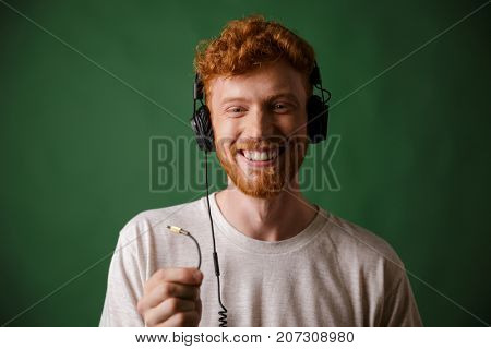 Close-up of young curly readhead hipster holding cord of headphones, looking at camera, over green background