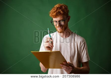 Smiling readhead bearded man in white tshirt holding folder and pen, over green background