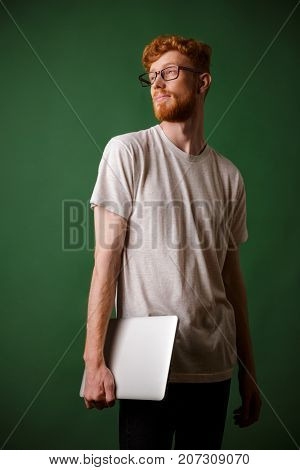 Shot of young bearded readhead hipster, holding laptop, looking away, over green background