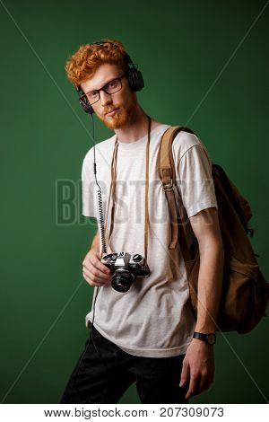 Yong readhead bearded hipster with backpack holding retro camera, listening to music, looking at camera, over green background
