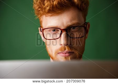 Cropped photo of serious young readhead man in glasses, working with laptop, over green background