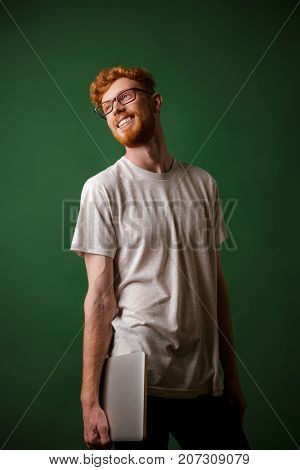 Portrait of young bearded readhead hipster, holding laptop, looking away, over green background