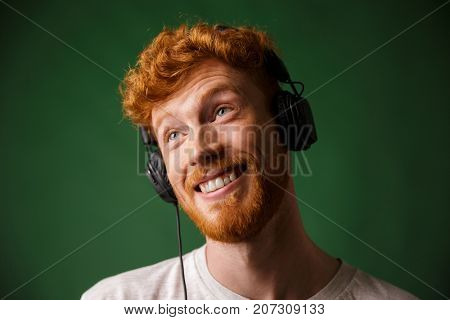Close-up portrait of happy hipster readhead man listening music in headphones, over green background