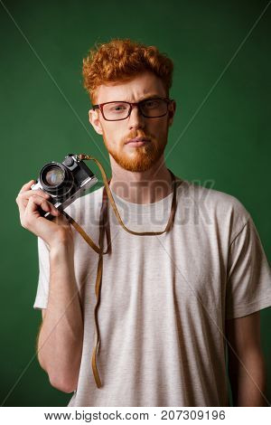 Portrait of serious readhead hipster photographer with camera isolated over green background
