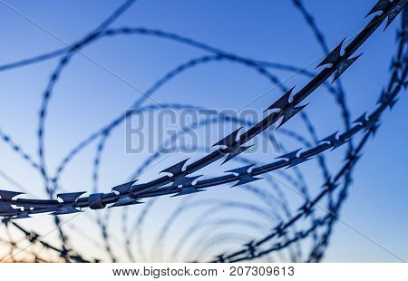 Fence with a barbed wire under a blue sky