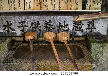 Kyoto, Japan - May 18, 2017: Row of bamboo ladles at a purificaton basin in front of the shinto temple