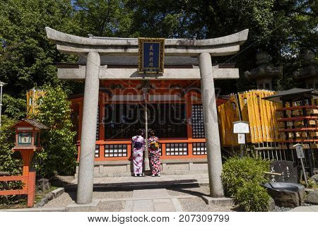 Kyoto, Japan - May 18, 2017:  Women in kimono in front of the sub shrine from Yasaka jinja behind the torii