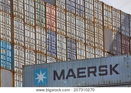 ROTTERDAM, THE NETHERLANDS - SEPTEMBER 15, 2017: Maersk containers stacked in a shipping terminal. Maersk is the largest container ship operator in the world since 1996.