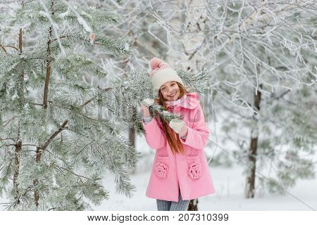 Girl outside in winter near Christmas tree