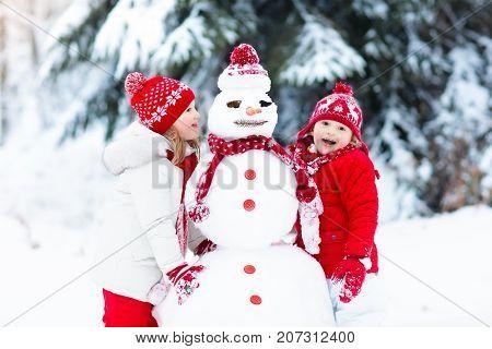 Kids Building Snowman. Children In Snow. Winter Fun.