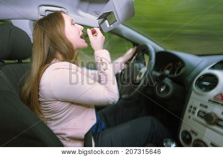 Young female driver using lipstick while driving a car