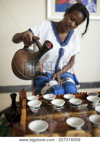 ADDIS ABABA, ETHIOPIA-OCTOBER 31, 2014: An unidentified woman pours coffee at a coffee ceremony in Addis Ababa, Ethiopia