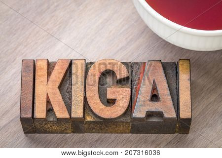 ikigai - Japanese concept  - a reason for being or a reason to wake up - word abstract in vintage wood type with a cup of tea
