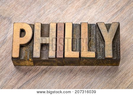 Philly (Philadelphia) word abstract in vintage  letterpress wood type against grained wooden background