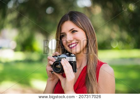 Smiling young woman using a vintage camera