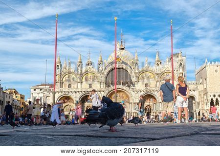 VENICE,ITALY - JULY 27,2017 : St Mark's Basilica in Venice with pigeons on the square on a summer day