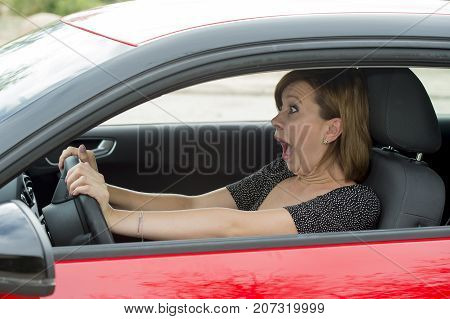 female rookie new driver young beautiful woman scared and stressed while driving car in fear and shock face expression screaming in panic
