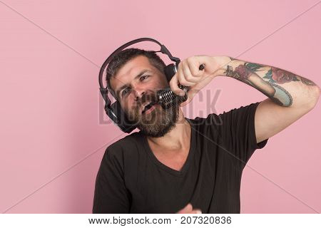 Technologies And Music Concept. Man Sings On Pink Background.