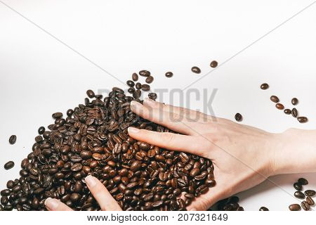 someone gathers a small handful of coffee beans