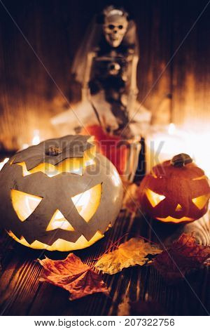 Halloween decorations. Spooky jack-o-lanterns burning in darkness and scull