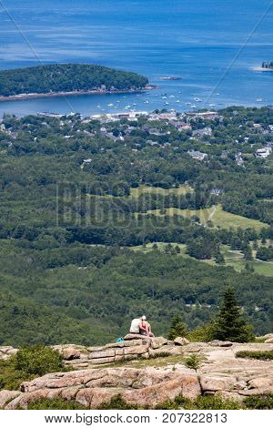 A couple sitting on a mountain looking at Bar Harbor in Maine, USA