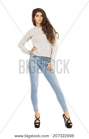 Fashion model in gray sweater and blue jeans, isolated on white studio