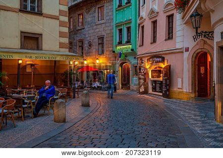 PRAGUE, CZECH REPUBLIC - SEPTEMBER 22, 2015: Outdoor restaurant on small evening street in Old Town of Prague - famous and popular tourist destination with more than 6 million visitors annually.