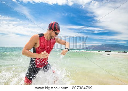Smartwatch triathlon swimming sport man finishing swim checking heart rate on smart watch. Male triathlete swimmer running out of ocean. Professional athlete in triathlon suit training for ironman.