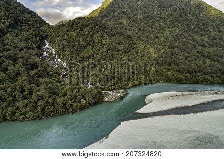 River nature landscape of New Zealand travel adventure. New Zealand aerial drone view from above of Haast River and Roaring Billy Falls waterfall in Mount Aspiring National Park, South Island.
