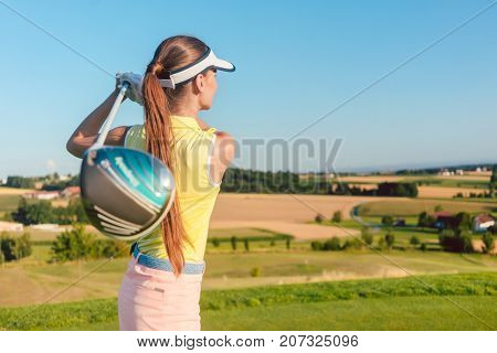 Young woman holding a driver club behind her back during golf swing, at the beginning of a professional match outdoors in a sunny day in the countryside