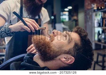 Side view headshot of a redhead bearded young man smiling ready for shaving in the hair salon, of a skilled barber with a classic straight razor in his hand
