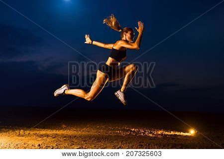 Young sports woman high jumping outdoors twilight training