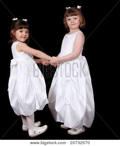 Adorable Zwillings-Schwestern in weißen Kleider Haolding Händen. isoliert auf