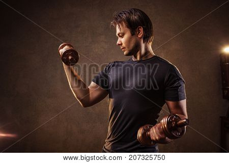 Young strong man with dumbbells on stone wall background