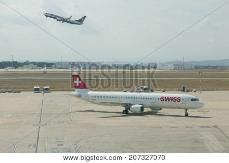 VALENCIA, SPAIN - SEPTEMBER 27, 2017: A Swiss Air Airliner taxing to the gate while a Ryan Air Airliner takes off in the background. Swiss Air is the national airline of Switzerland.