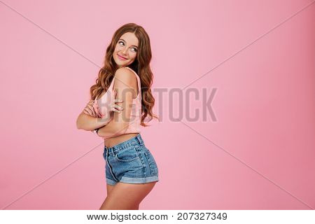 Portrait of a lovely smiling woman in summer clothes posing while standing and looking away at copy space isolated over pink background